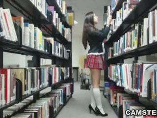 Schoolmeisje in uniform wants naar bust uw nut in de bibliotheek