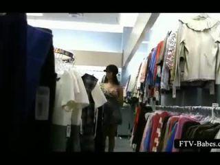 Brunete amatieri dares līdz berzēt viņai cunt uz a apģērbi veikals