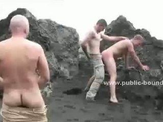 College gay guy bound in ropes on beach
