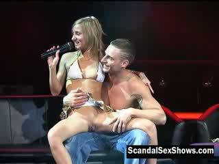 Blondie meitene gives instructions par cik līdz lūdzu a meitene uz priekšējais no an audience