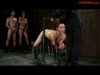 Flicka tied till metal ram i doggy getting henne fittor och mun körd av husmor med strapon och mästare i den fängelsehåla
