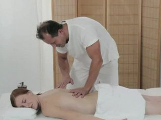 Pale redhead fucked by masseur on a table