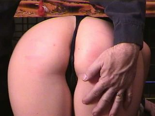 Soft young brunette in bustier gets caned on ass by older ponytailed dude
