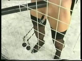 Naughty girl in a jail got her big metal clamps with heavy w