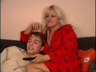 Mama dan putra menonton televisi di kursi sofa