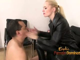 Dominante in zwart leder spelen met een slaaf