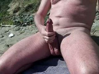 Alasti homo näyttää kukko päällä the nudisti ranta