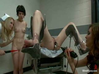 Two reged pussys have strapped to a gyno chair and bumped by their lesbie doctors